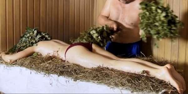 веником гладит тело девушки