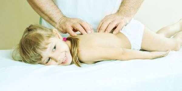 маленькой девочке делают массаж спины
